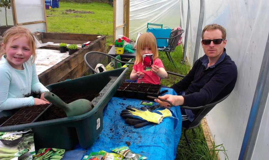 Leo, Em and Lucy planting seeds in the polytunnel